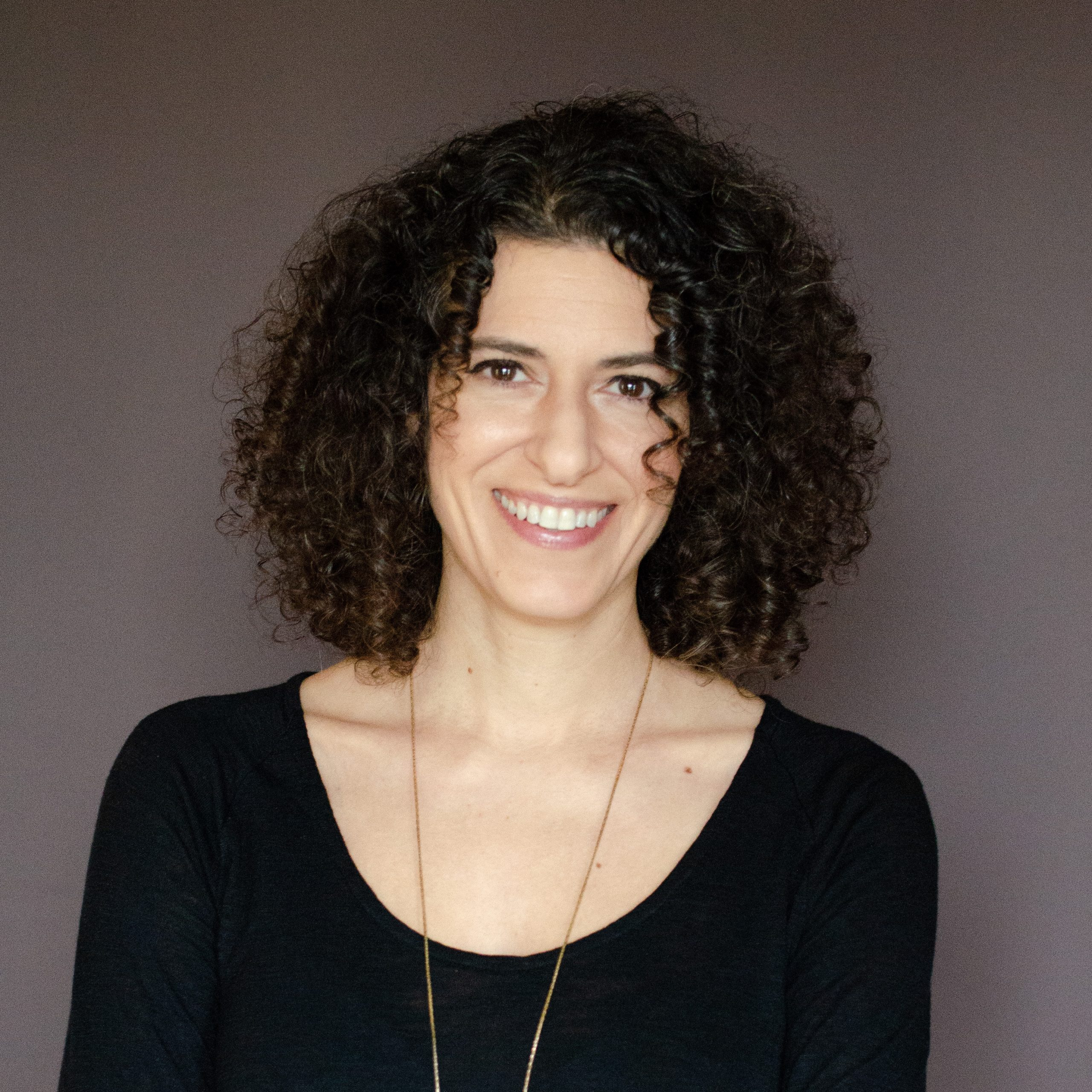 Woman with a black top and curly hair standing in front of a blank wall