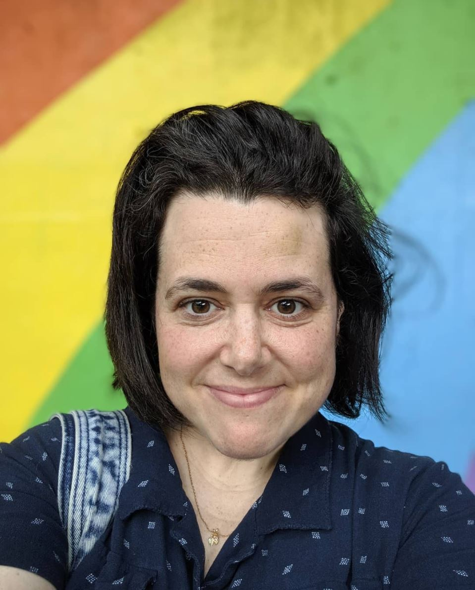 Woman with black hair standing in front of a colourful rainbow wall